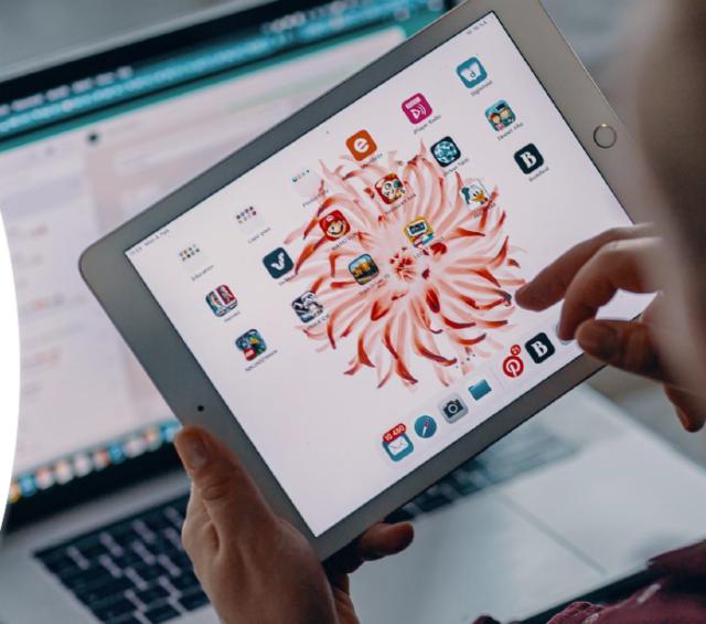 Henkilöllä on käsissään tablettilaite, ja taustalla näkyy tietokoneen näyttöä.