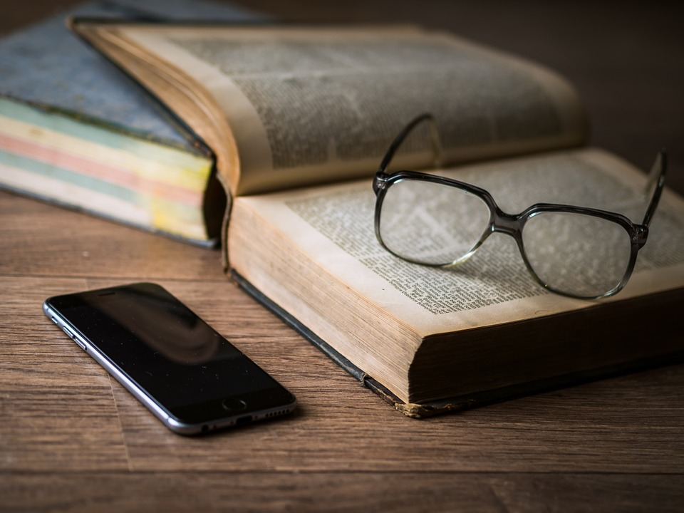 kirja, silmälasit ja puhelin