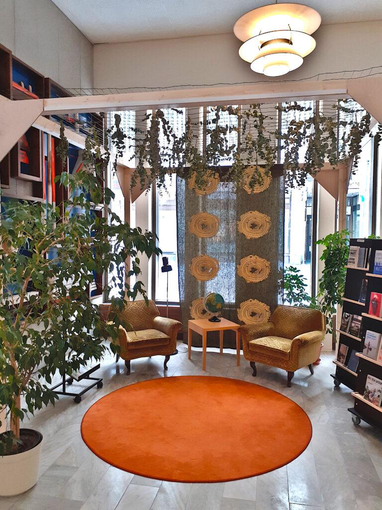 Vihreässä nurkkauksessa on oranssi pyöreä matto, kaksi nojatuolia, lukuvalo ja pieni pöytä. Takana olevassa tummassa pellavakankaassa on vaaleita tyyliteltyjä puun leikkauskuvia. Tilassa on runsaasti viherkasveja. Det gröna hörnet består av en orange rund matta, två fåtöljer, läslampa och ett litet bord. Det mörka linne har ljusa möster som ser ut som en skärd träd med sina årsringar. Det finns mycket grönväxter i gröna hörnet.