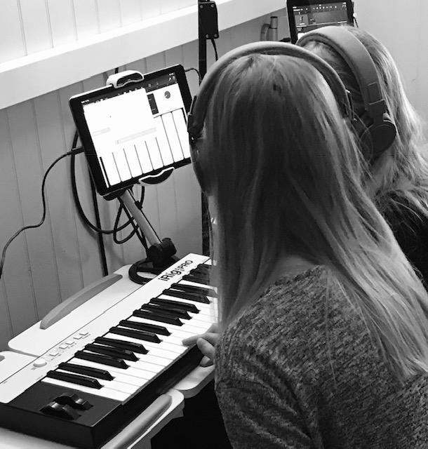 Kaksi tyttöä harjoittelee musiikin tekoa Ipad ja sähköpiano apunaan