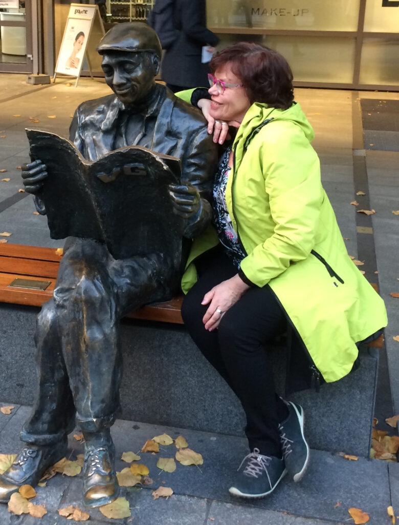 Anneli Ketonen istuu penkillä sanomalehteä lukevan miehen patsaan vieressä nojaten hymyillen patsaan olkapäähän. Anneli Ketonen sitter på bänken bredvid en staty av en man som sitter och läser en tidning. Anneli ler och luter mot statyns axel.