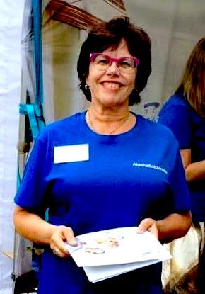 Anneli Ketonen seisoo iloisena sininen t-paita päällään ja esitenippu kädessään SuomiAreenan tapahtumapaikalla. Anneli Ketonen står i SuomiAreenas händelseplats i en blå t-skjorta och en bunt broschyrer i sin hand och ser glad ut.