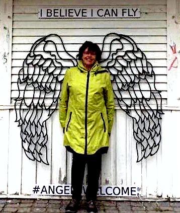 Anneli Ketonen seisoo suoraan kameraan päin vasten valkoista seinää jossa on metalliset enkelinsiivet. Hänen yläpuolellaan on teksti: I Believe I Can Fly. Anneli Ketonen står mot fotografen och hon har ängelvingar som är fast i väggen som är bakom henne. Ovanför står det I Believe I Can Fly.
